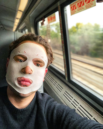 Garrett Munce on train with facial mask